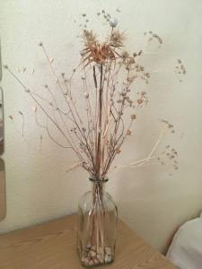 Flores secas y piedras de un camino + botella reutilizada para decorar.