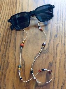 Colgador de gafas casero con bolas reutilizadas.